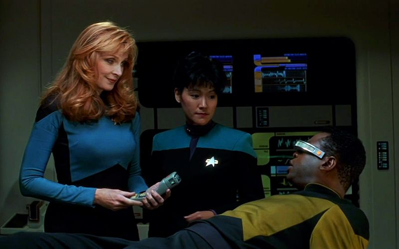 Dr Crusher examines a patient on the Enterprise